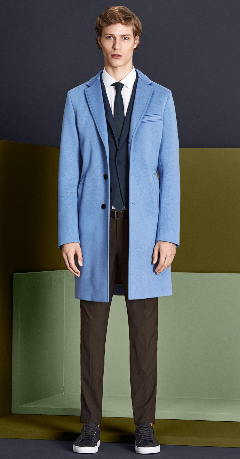 Mantel in Pastellblau, dunkelblaues Sakko, weißes Hemd, khakifarbene Hose mit dunkelblauer Krawatte, grünem Gürtel und grünen Schuhen von BOSS