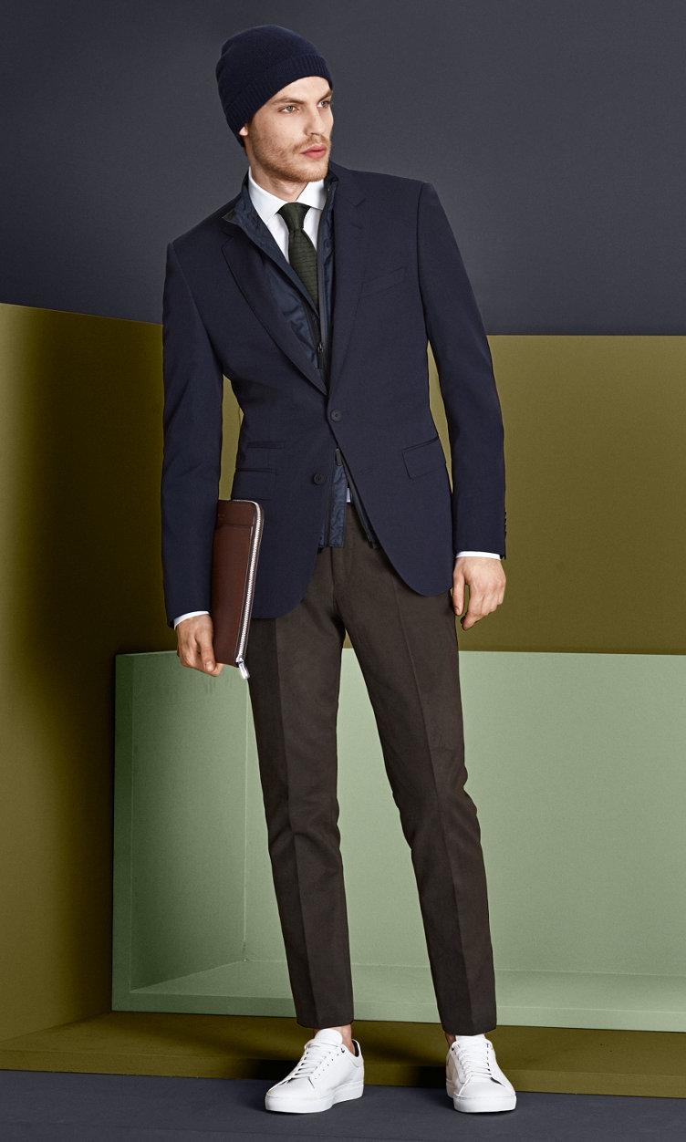 Dunkelblaue Jacke, weißes Hemd, dunkelbraune Hose mit dunkelblauer Mütze, khakifarbener Krawatte, hellbrauner Tasche und weißen Schuhen von BOSS