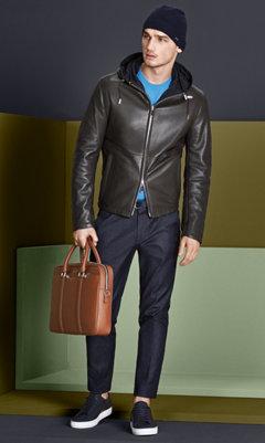 Khakifarbene Lederjacke, blauer Strick, dunkelblaue Hose mit dunkelblauer Mütze, Gürtel, brauner Tasche und dunkelblauen Schuhen von BOSS