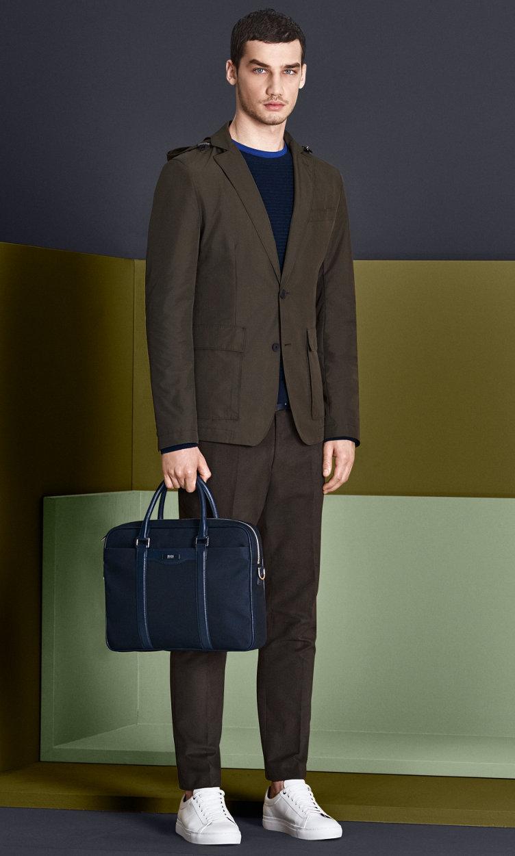 Khakifarbenes Sakko, dunkelblauer Strick, hellblaues Jersey, khakifarbene Hose mit schwarzer Tasche und weißen Schuhen von BOSS