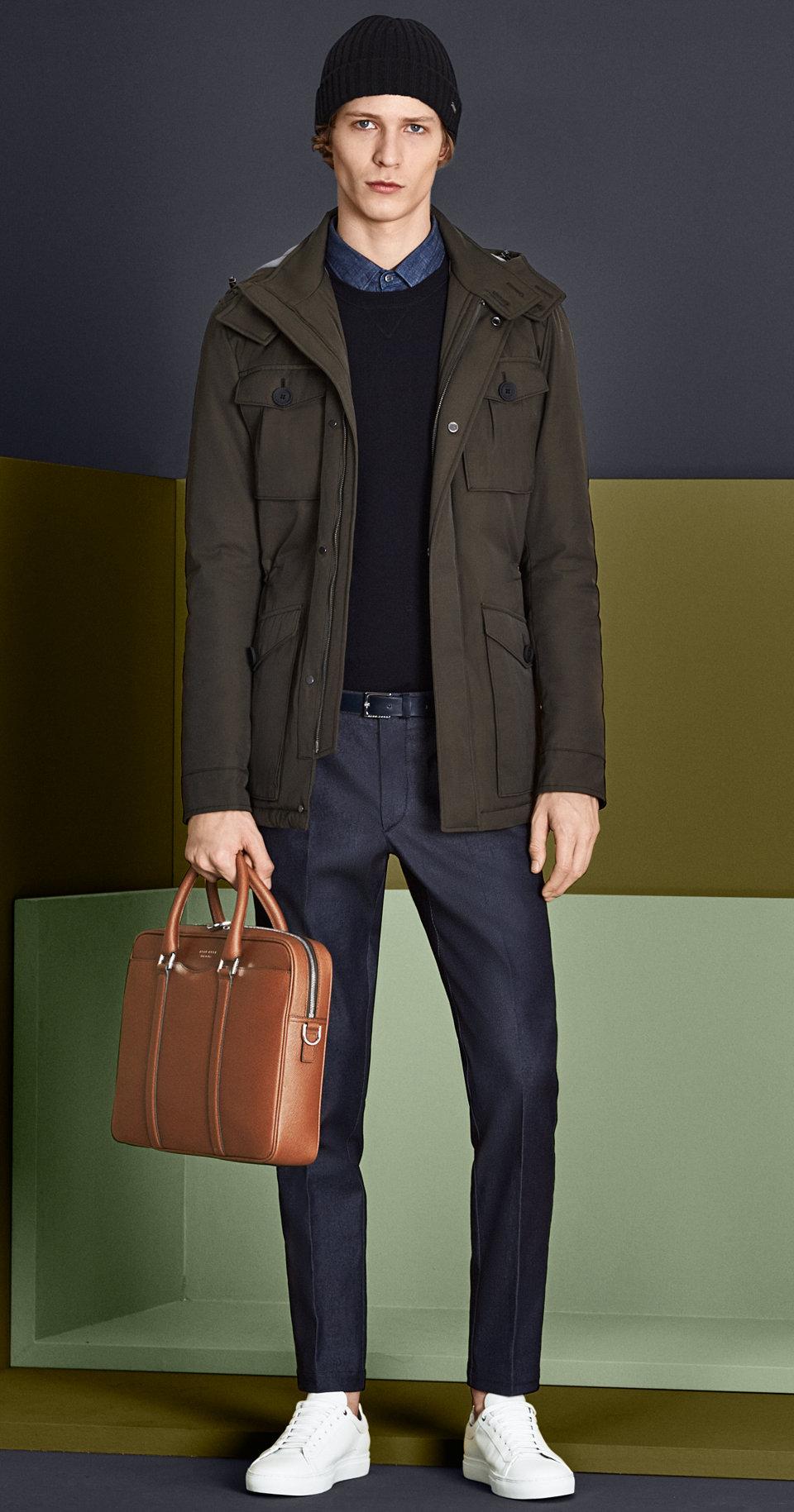 Khakifarbene Jacke, Strick und Hemd in Dunkelblau, dunkelblaue Hose mit dunkelblauer Mütze, Gürtel, khakifarbener Tasche und weißen Schuhen von BOSS