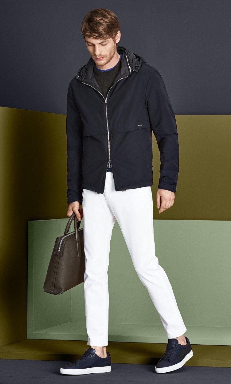 Dunkelblaue Jacke, dunkelbrauner Strick, weiße Jeans mit blauem Gürtel, khakifarbener Tasche und blauen Schuhen von BOSS