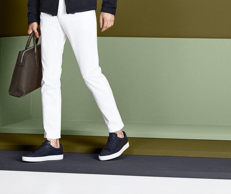Model in moderner HUGO BOSS Jeans in Dunkelblau. Kombiniert mit passenden Sneakern, Tasche und Jacke.