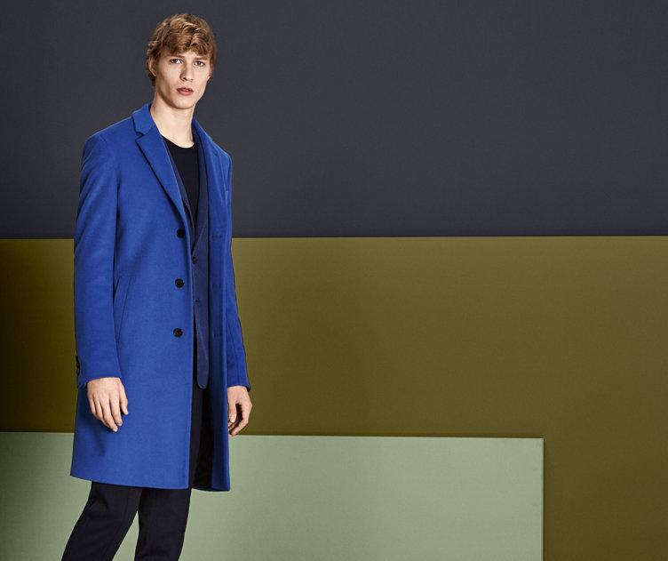 Model met omkeerbare mantel van nylon. In zwart en in een statementmotief in groen, wit, zwart en grijs. Gecombineerd met een zwarte tas en een kostuum.