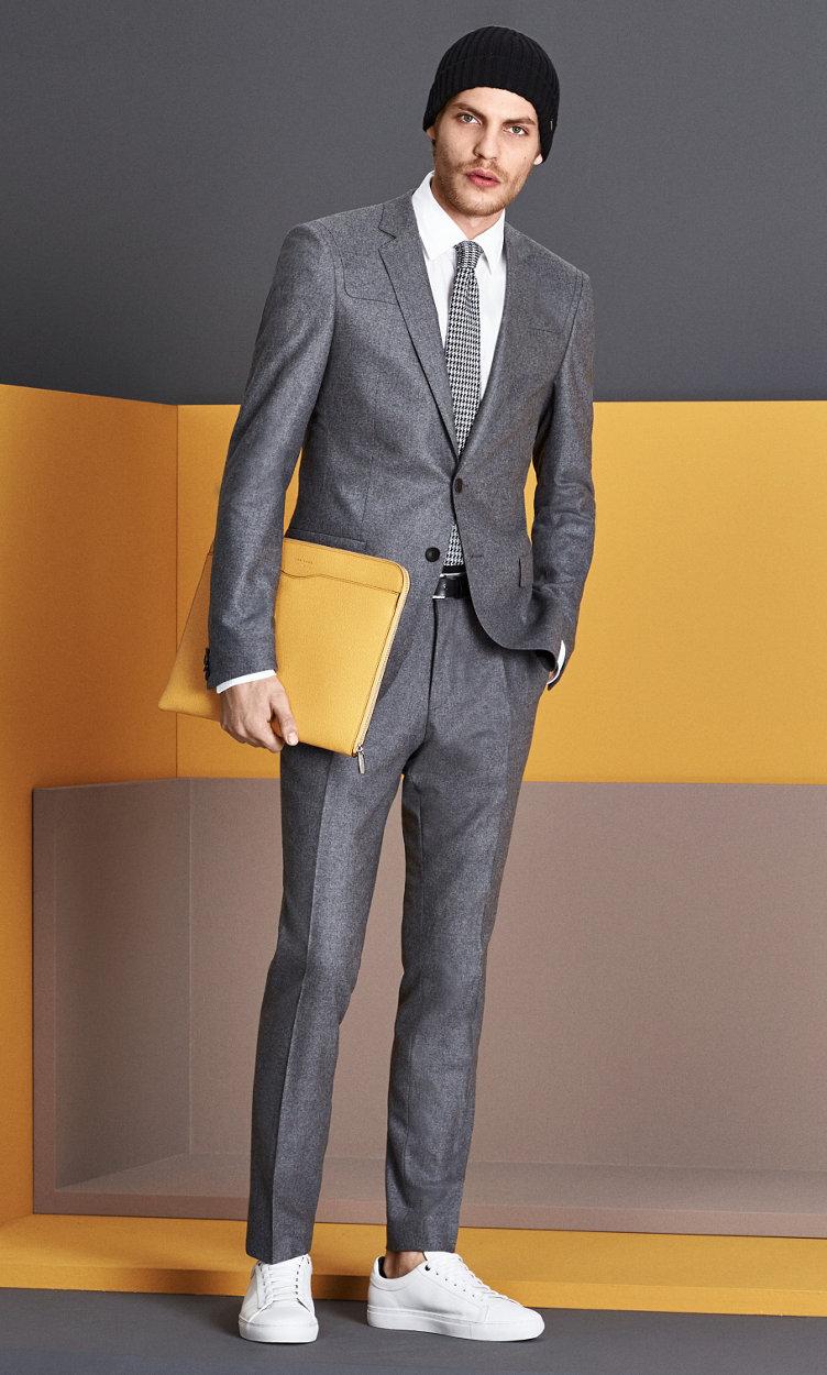 Grijs colbert, grijze broek, wit overhemd, gele tas, stropdas en schoenen van BOSS