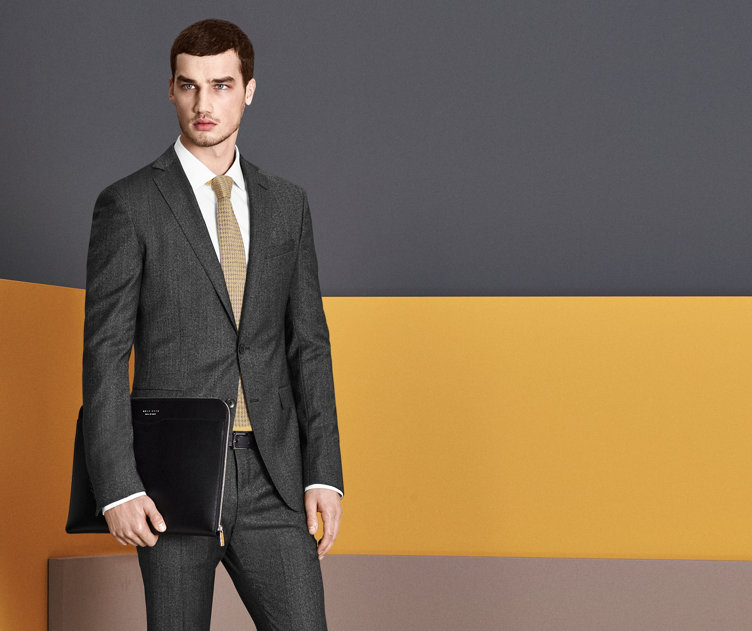 Anthracite suit, white shirt and yellow patterned tie with a black leather tablet sleeve by BOSS