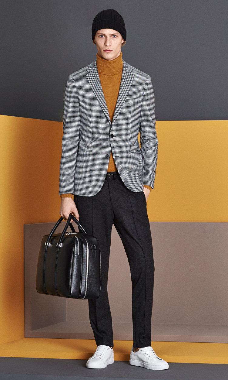 Grijs colbert, gele gebreide trui, grijze broek, muts, tas en schoenen van BOSS