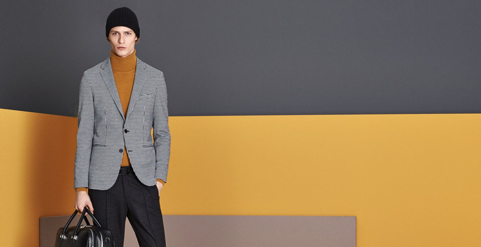 Anthracite tailored jacket, gold knitwear and black trousers with a black hat and bag ba BOSS