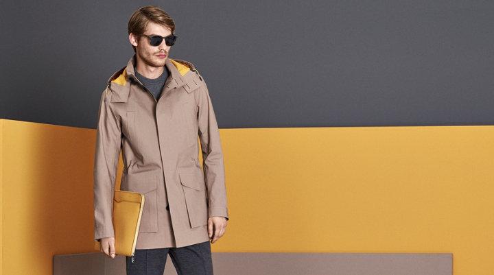Jas in naturel, grijze gebreide trui, grijze broek, gele tas en zonnebril van BOSS