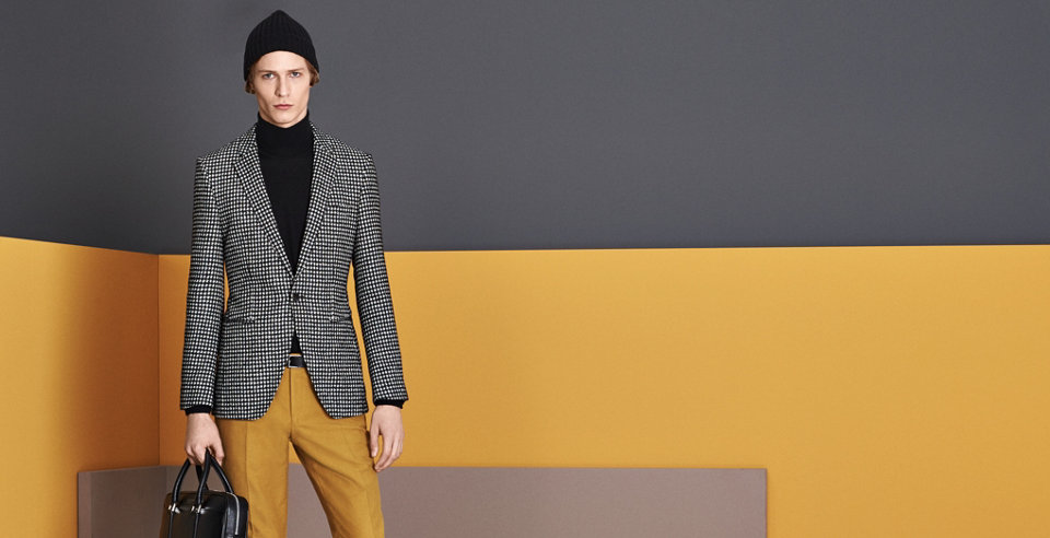 Anthracite blazer, nlack knitwear, gold trousers and black hat and bag by BOSS