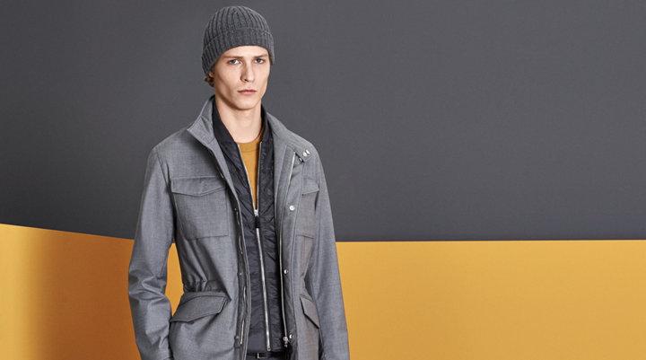 Grijze jas over gele gebreide trui met grijze broek, een zwarte muts en witte schoenen van BOSS