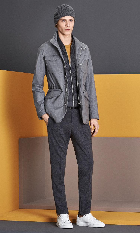 Grijze jas, gele trui, grijze broek, muts en schoenen van BOSS