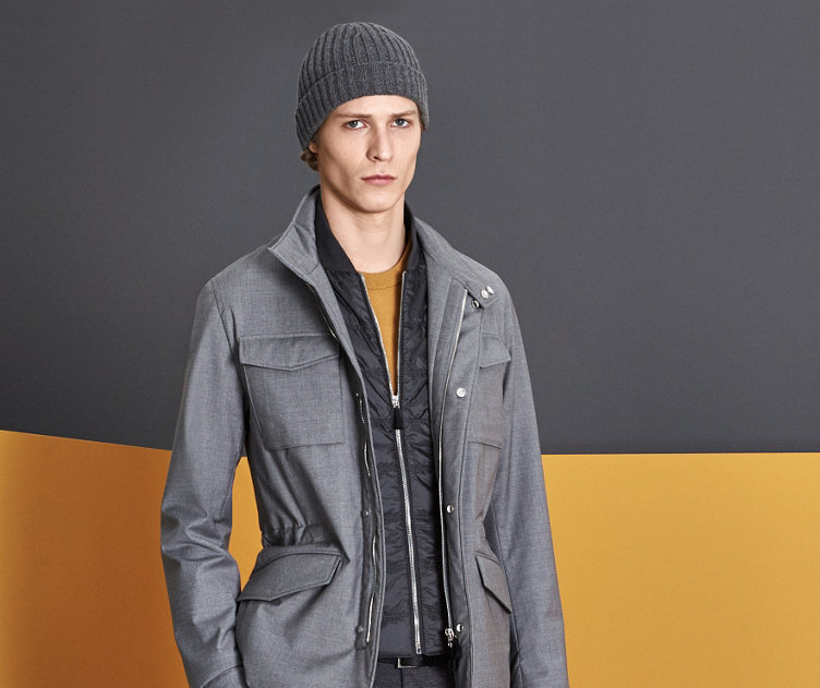 Graue Jacke über gelbem Oberteil aus Strick, graue Hose, schwarze Mütze und weiße Schuhe von BOSS