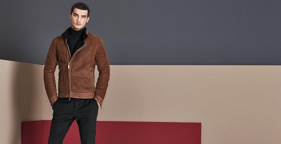 Model trägt schwarze Lederjacke aus weichem Leder und blaue Hose, blaue Ledertasche und moderne Sonnenbrille.