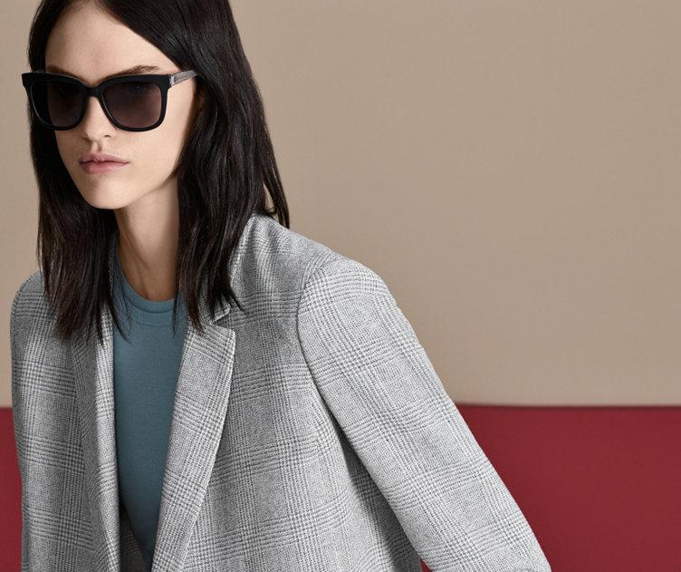 Model met zonnebril van HUGO BOSS. Gedurfd ontwerp met donker montuur en lichte details.