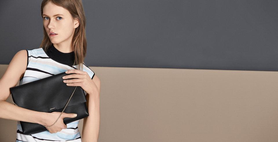 Drie handtassen van HUGO BOSS, van leer. Gepresenteerd op een rij in de moderne kleuren lichtgeel, zwart en roze.