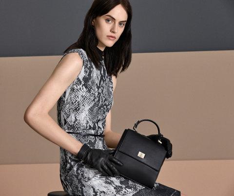 Zwart-grijze jurk met slangenprint, zwarte handschoenen en een zwarte tas van BOSS
