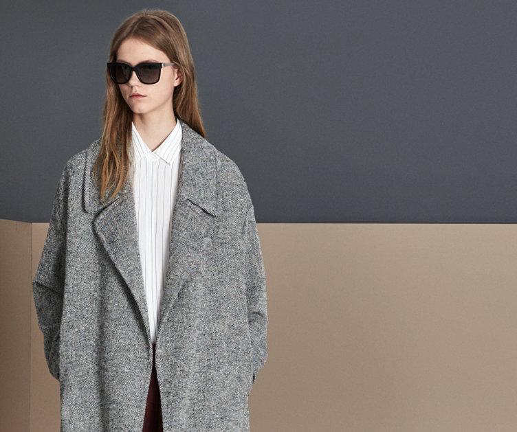Le mannequin porte un chemisier en soie HUGO BOSS ajusté blanc. Associé à des lunettes de soleil foncées et un pantalon noir.