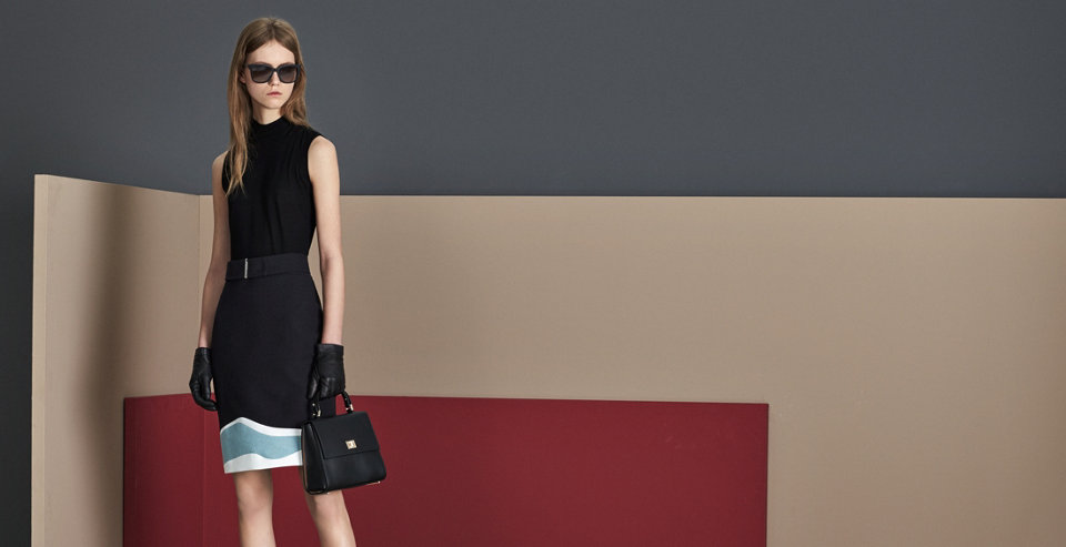 Model in hellgrauem Bleistiftrock von BOSS. Der Rock wird mit einer blaugrau gemusterten Bluse und einer schwarzen Handtasche kombiniert.