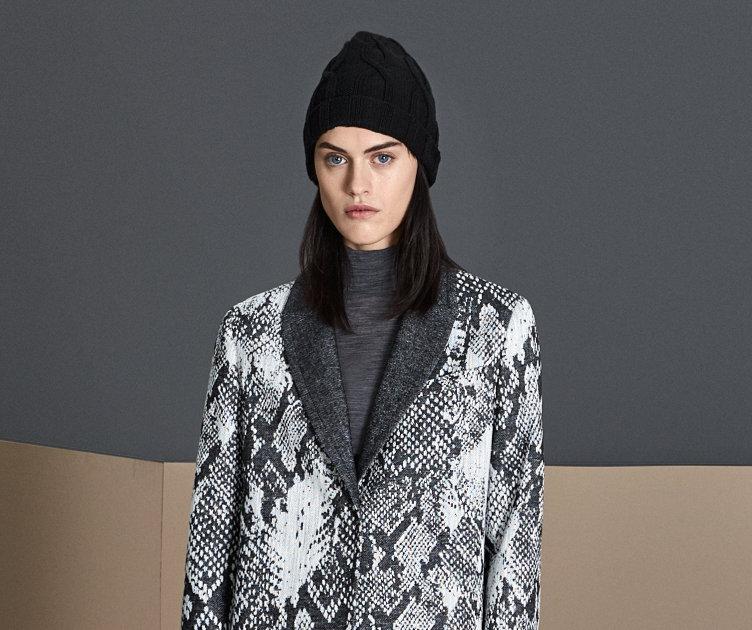 Dunkelgrauer Mantel über braunem Oberteil aus Strick mit grauer Mütze von BOSS