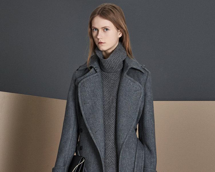 Grijze mantel over grijze gebreide trui met grijs-witte rok, zwarte leren tas en zwarte sneakers van BOSS