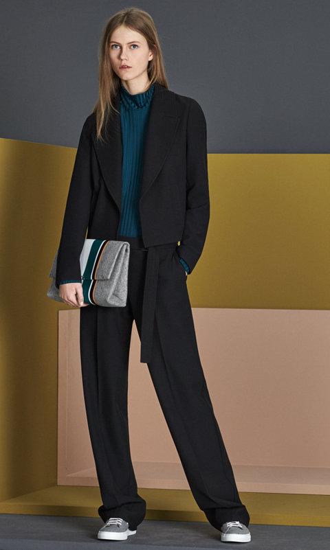 Schwarze Jacke über dunkelgrünem Jersey mit einer schwarzen Hose, schwarzen Schuhen und einer grauen Tasche von BOSS