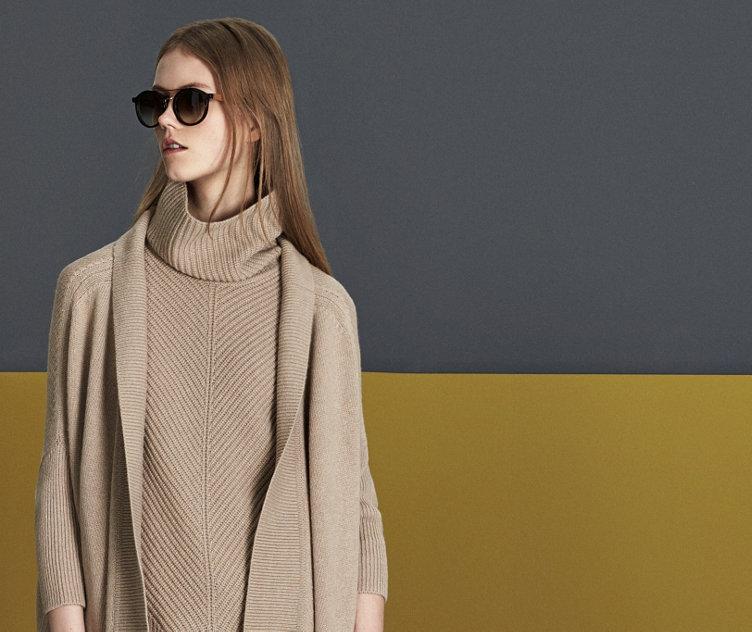 Le mannequin porte un élégant pull HUGO BOSS blanc à basque. Ajusté. Associé à une jupe crayon noire et un sac à main.