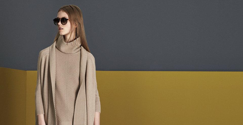Model in elegantem HUGO BOSS Schößchenpullover in Weiß. Tailliert. Kombiniert mit Bleistiftrockund Handtasche in Schwarz.