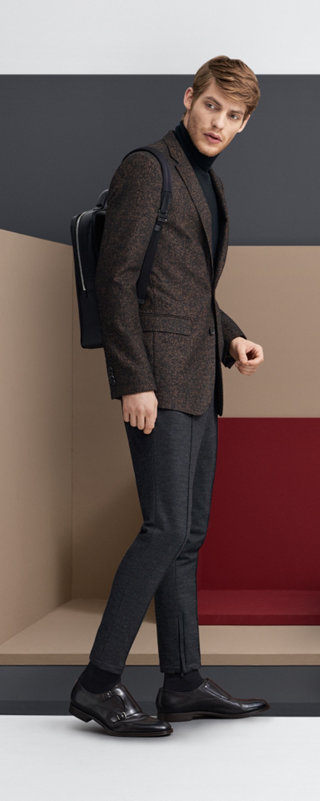 Brown Jacket over black trousers and black backpack by BOSS