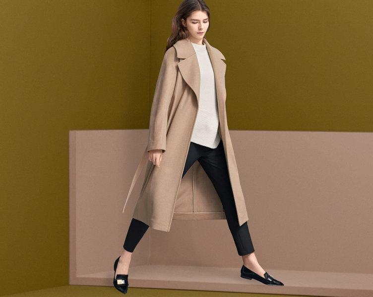 Naturfarbener Mantel über weißem Strick mit einer schwarzen Hose und schwarzen Schuhen von BOSS