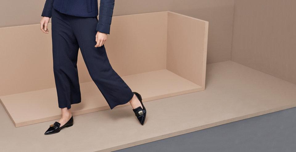 Model in flachen Sandalen von BOSS aus schwarzem Leder. Kombiniert mit blauer Hose, weißem Cardigan und schwarzer Tasche.