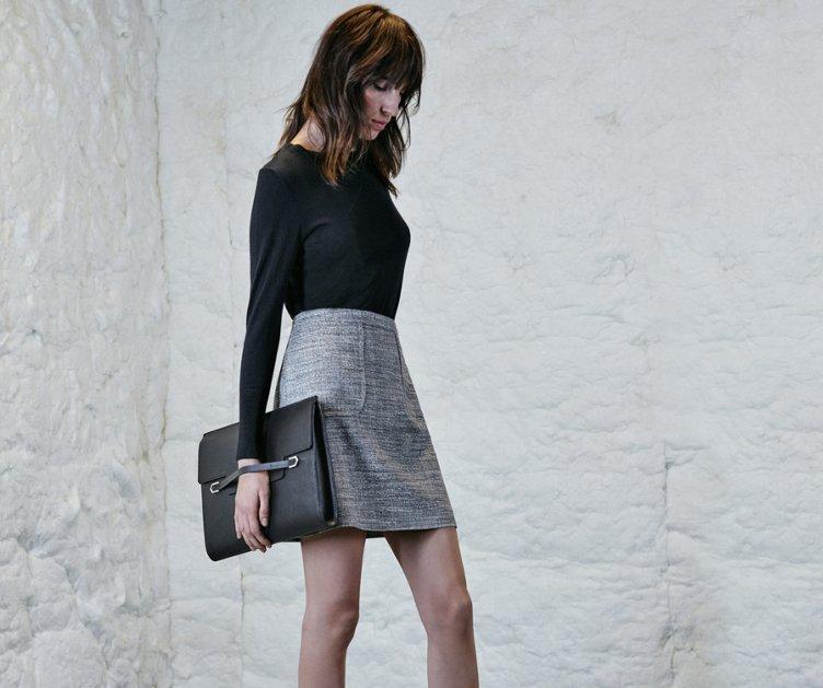 Black knitwear, patterned skirt and black bag by HUGO
