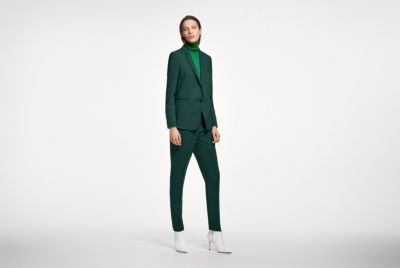 Female model is wearing a dark green suit together with green knitwear from BOSS