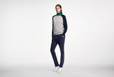 La donna indossa un capo in maglia abbinato a pantaloni e tacchi alti by BOSS Donna