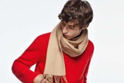Le mannequin porte un pull rouge et une écharpe beige BOSS