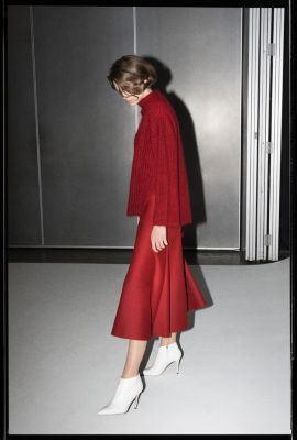 Female model is wearing dark red knitwear together with a red skirt from BOSS