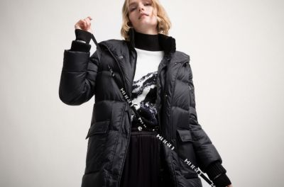Vrouwelijk model draagt een zwarte mantel met gebreide inzet, trui met bergdessin in jacquard en zwarte broek van HUGO