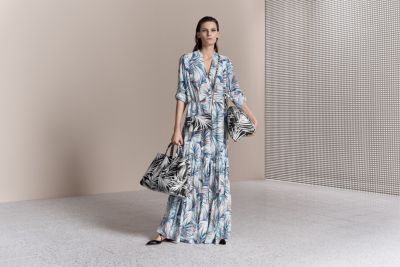 Woman is wearing maxi dress paired with bags from BOSS