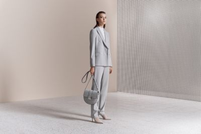 Woman is wearing jacket, knitwear and trousers paired with high heels and bag from BOSS
