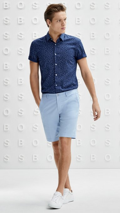 ae79f4cb7 Man in printed short sleeve shirt, light blue shorts, and white sneakers by  BOSS ...