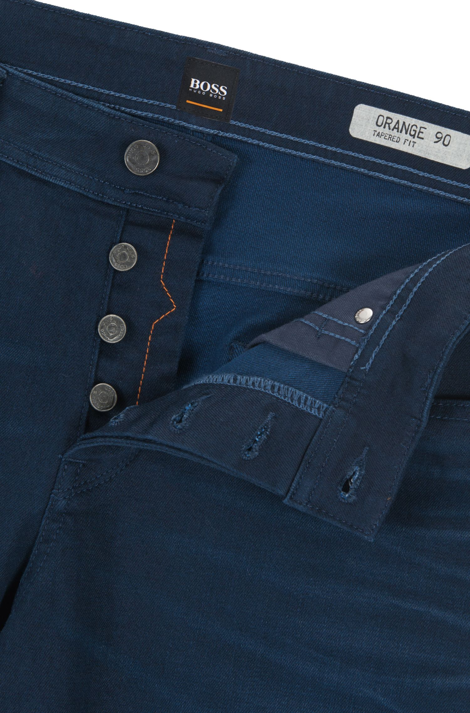 Vaqueros tapered fit en denim elástico con tono añil doble