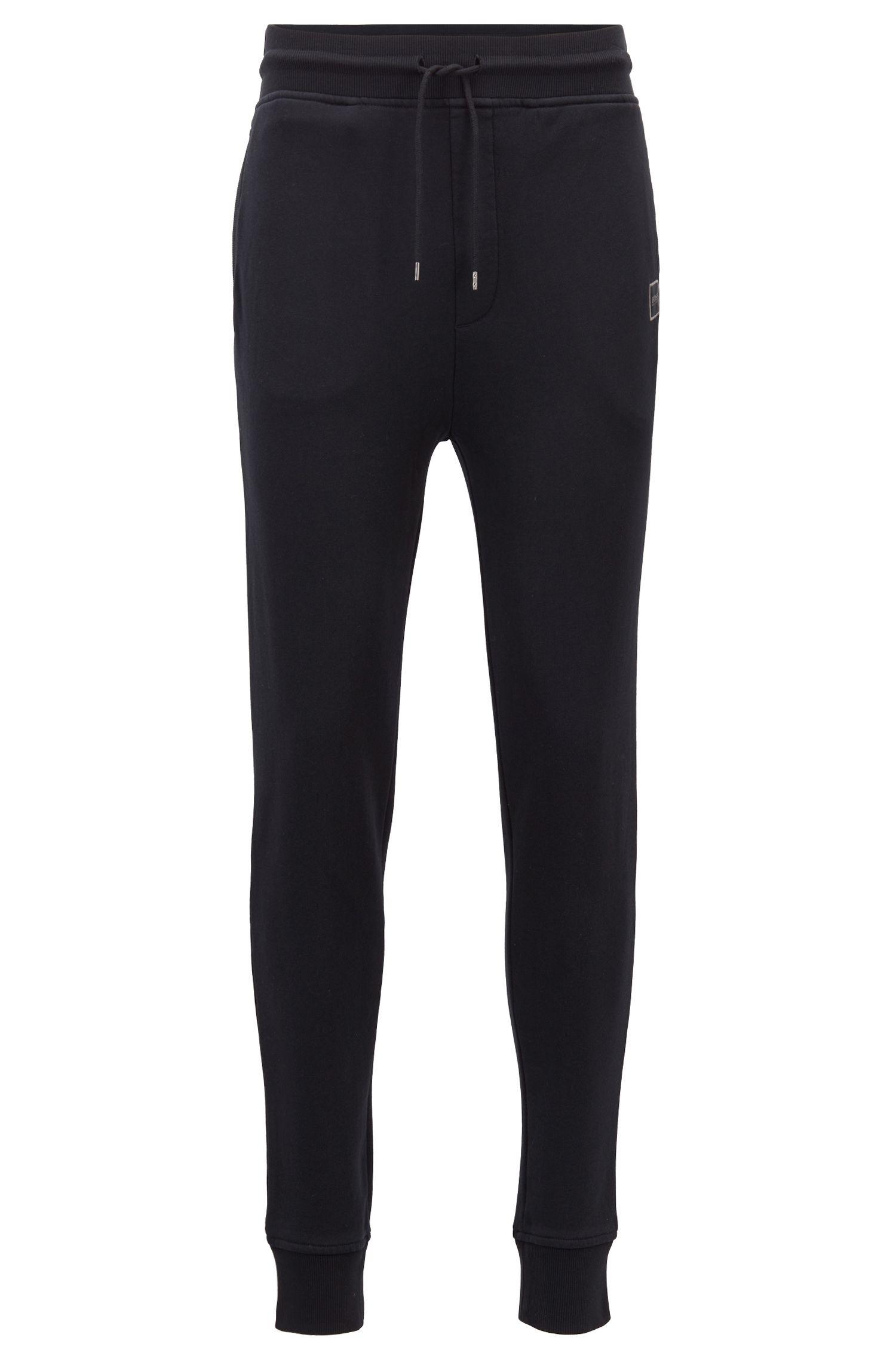 Pantalon de jogging resserré au bas des jambes en molleton French Terry, avec logo tissé, Noir