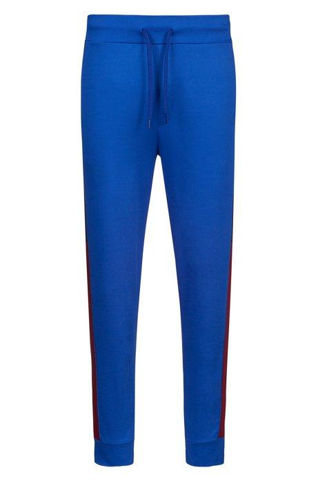 Pantalon Regular Fit en jersey à imprimé logo et design color block, Bleu