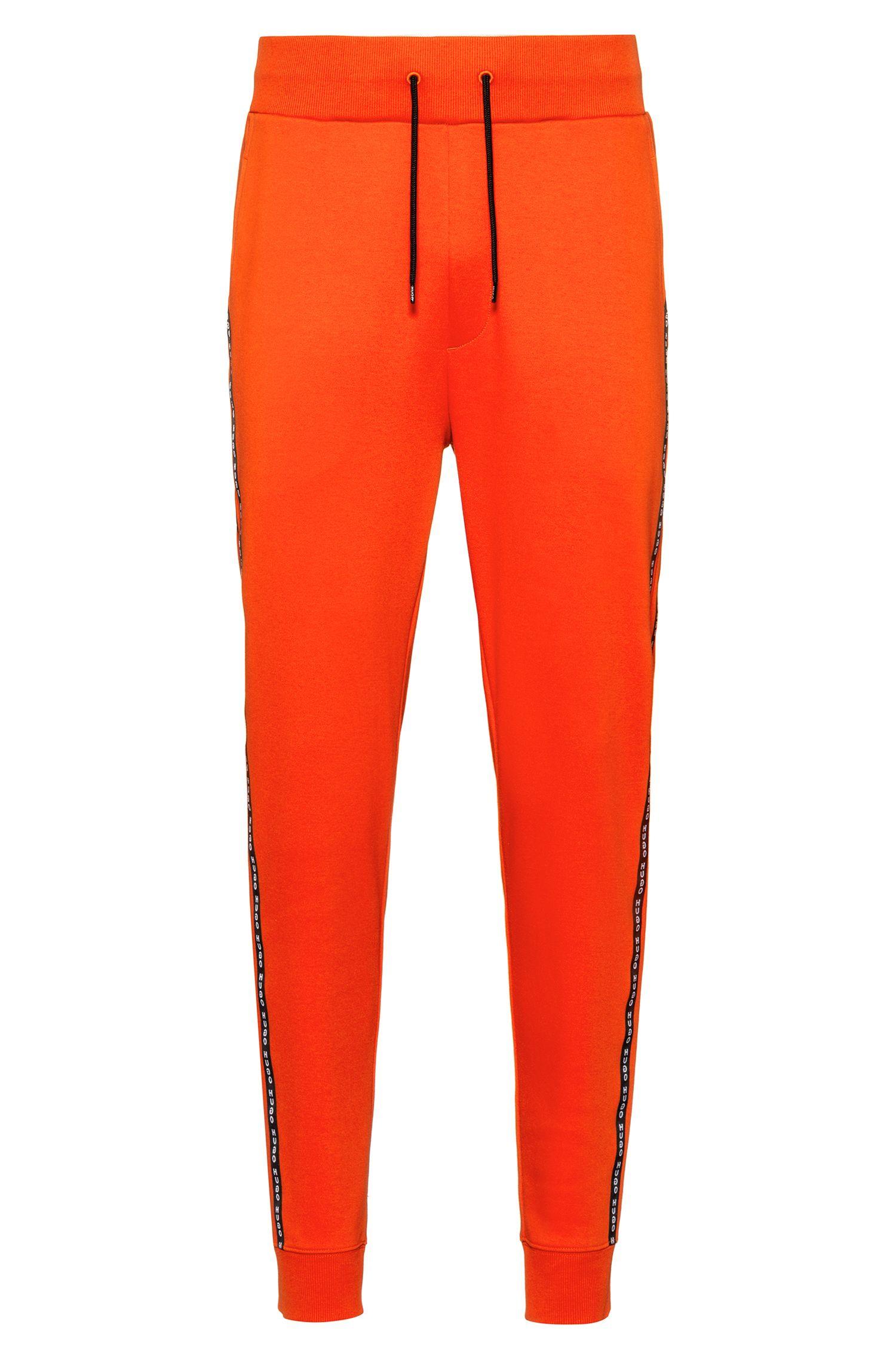 Pantalon en coton interlock resserré au bas des jambes, avec rubans logo sur les coutures latérales, Orange