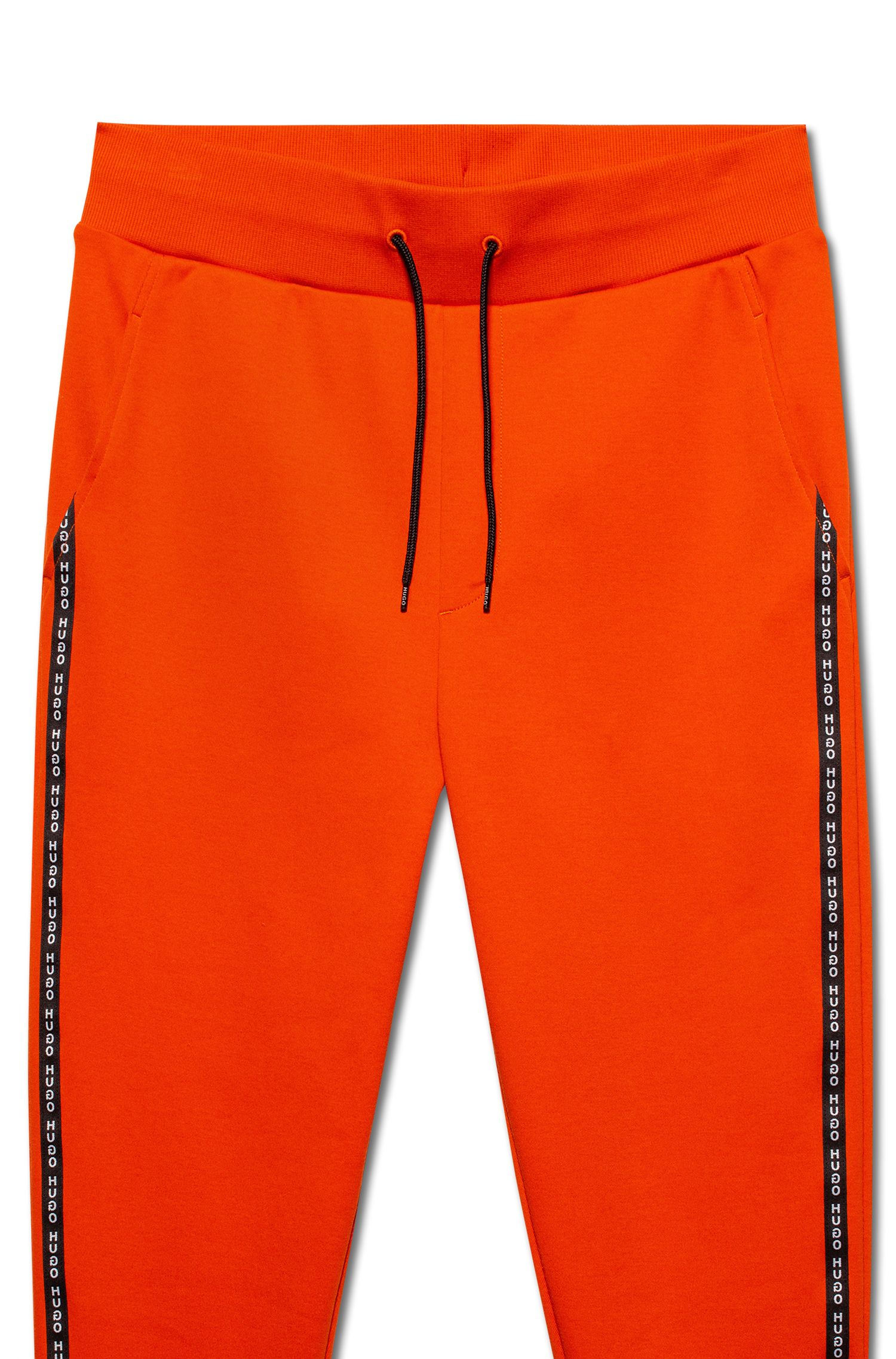 Pantalones de algodón interlock con puños en los bajos y cinta con logo en las costuras laterales, Naranja