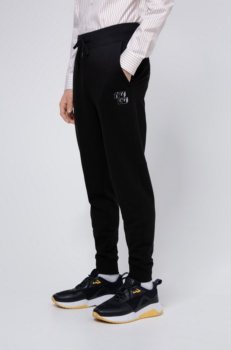 Cuffed French-terry jogging trousers with cubistic logos, Black