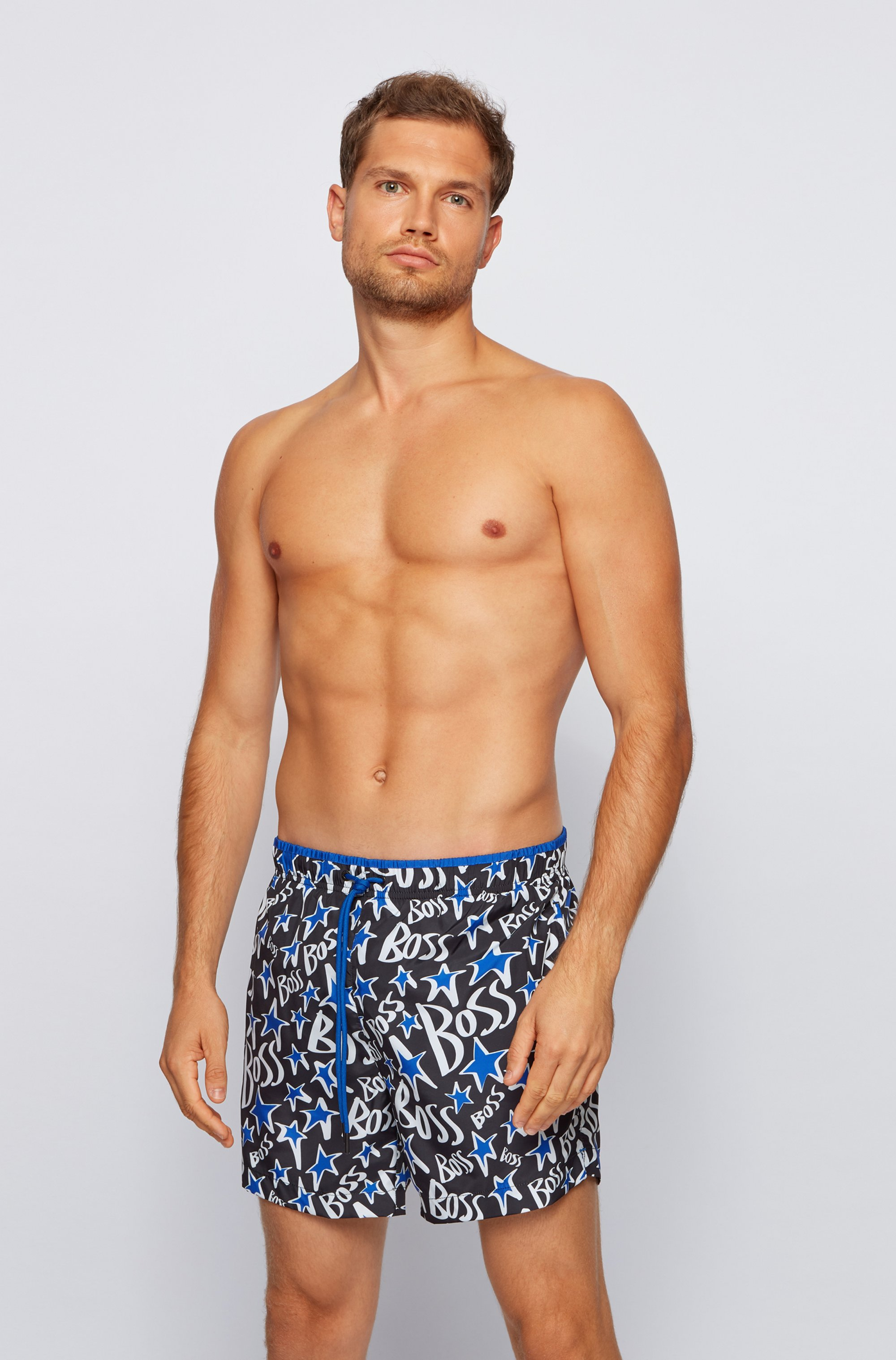 Quick-drying swim shorts with stylised stars and logos