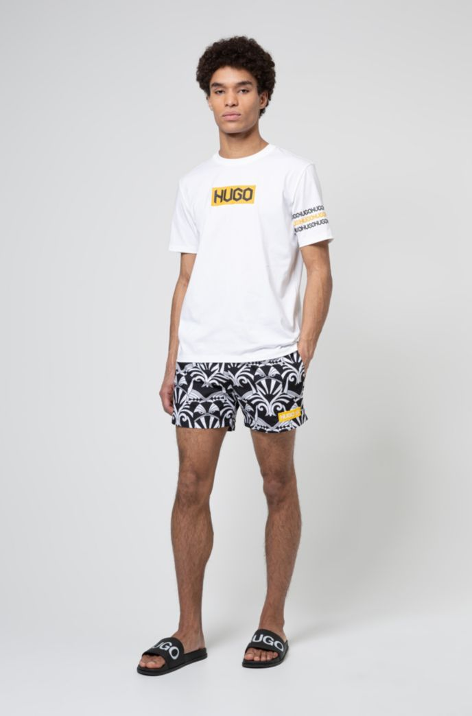 Quick-dry short-length swim shorts with collection artwork