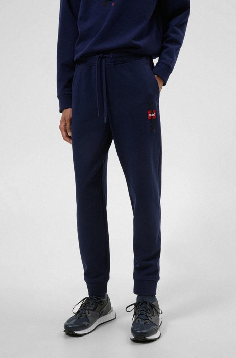 French-terry tracksuit bottoms with logo and calligraphy artwork, Dark Blue