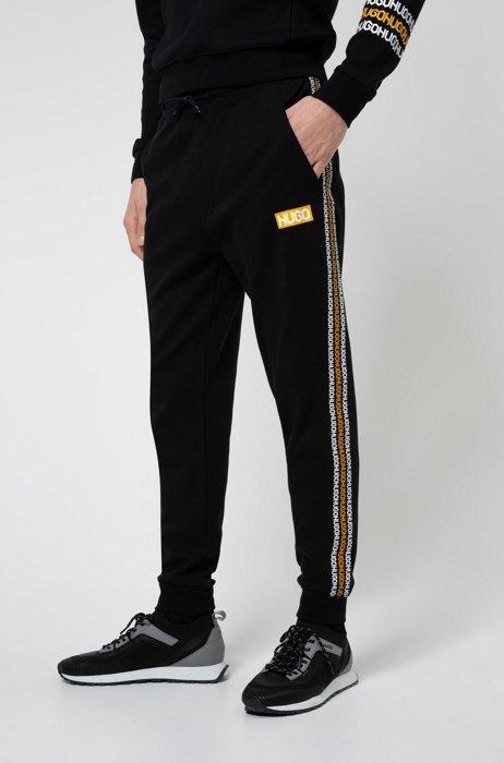 Trainingsbroek van katoenen sweatstof met logoprints in bandafdruk-stijl, Zwart